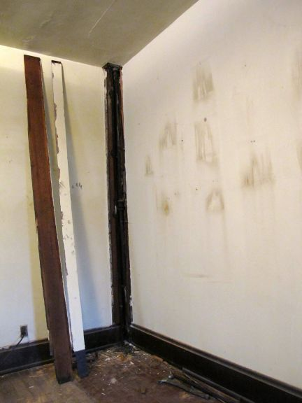 The wood planks removed, exposing the supply and drain pipes.
